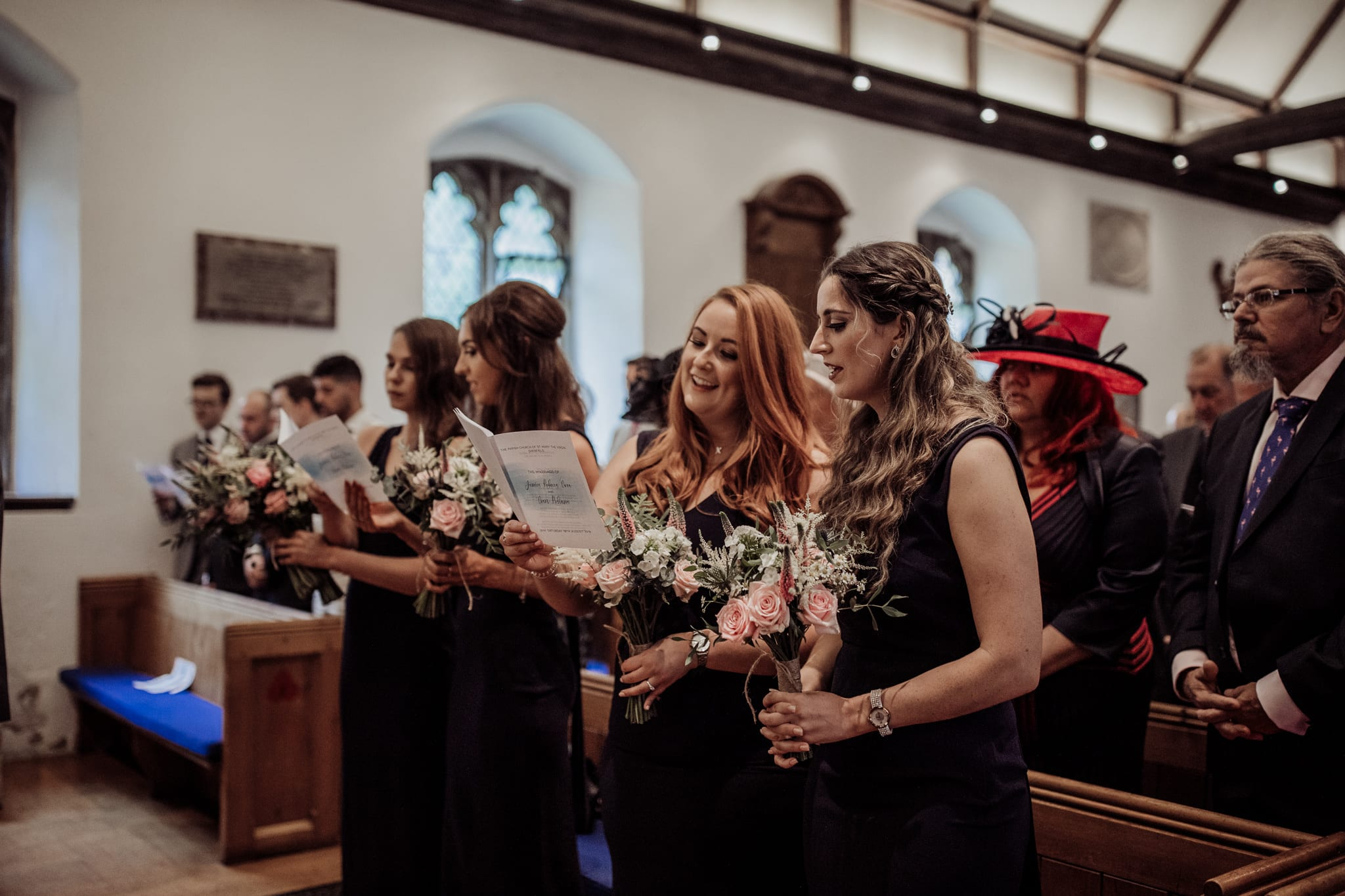 bridesmaids singing during church ceremony