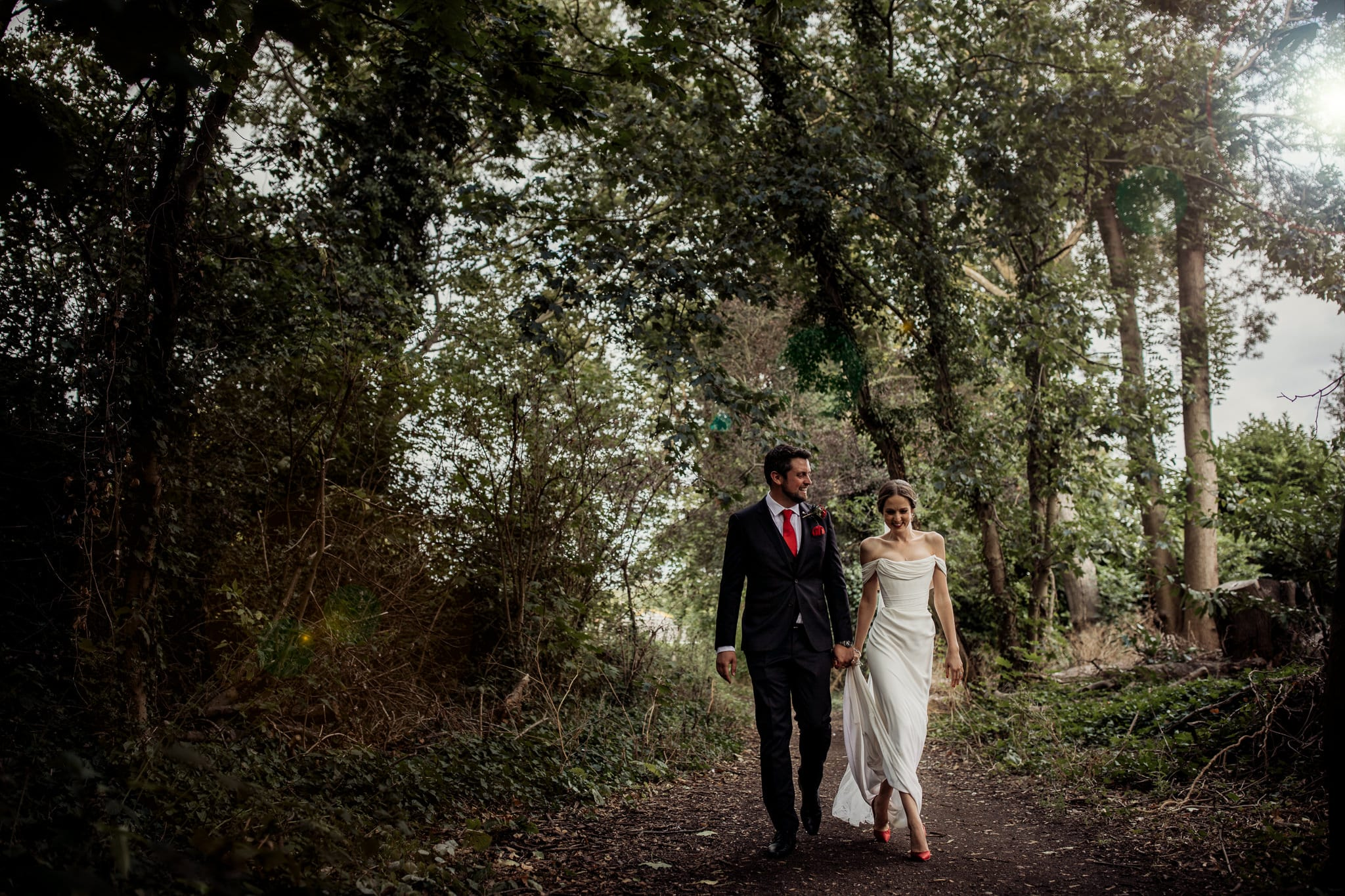 subride and groom walking in a forest