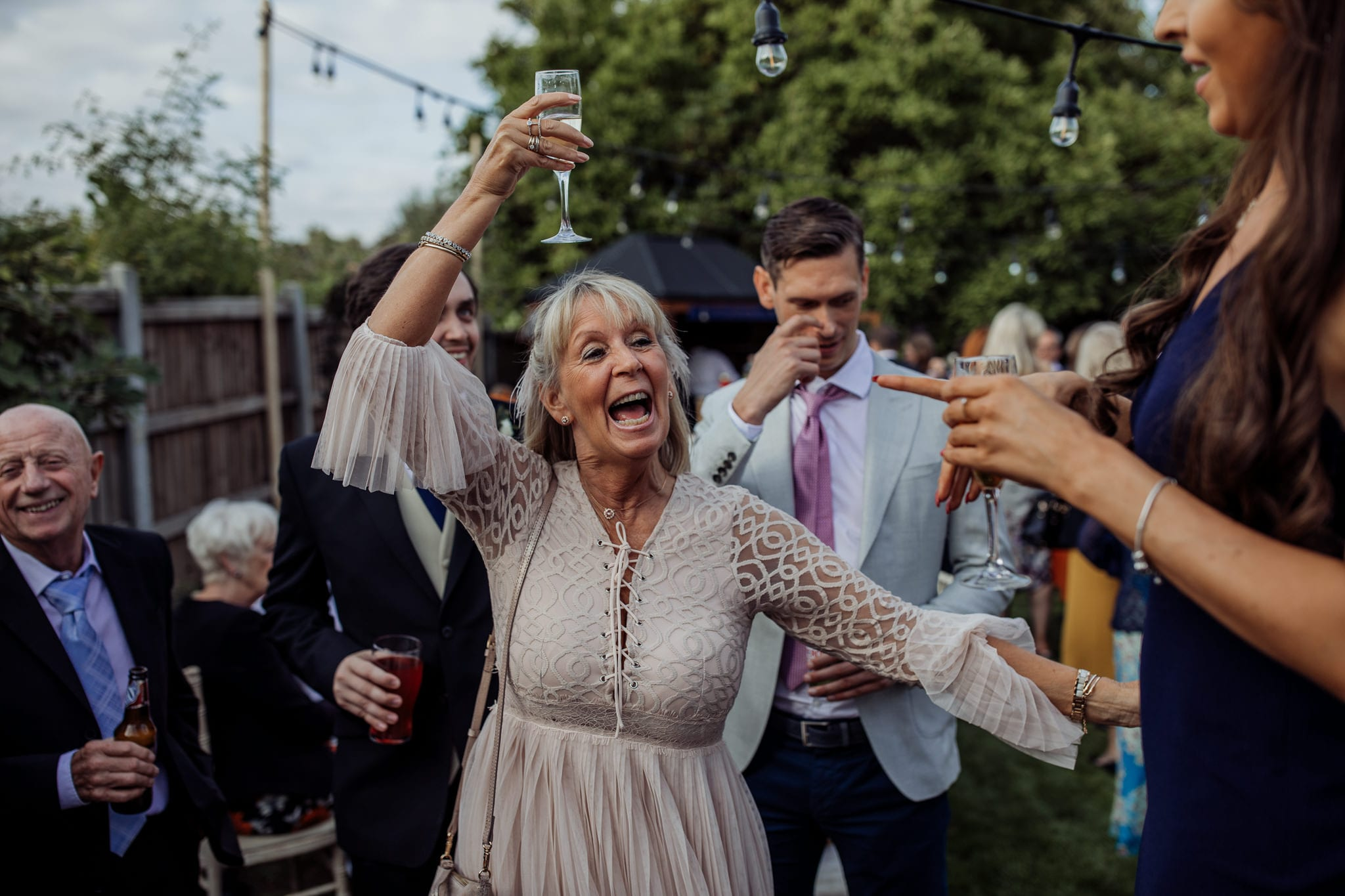 lady cheering with champagne glass at an Essex back garden wedding