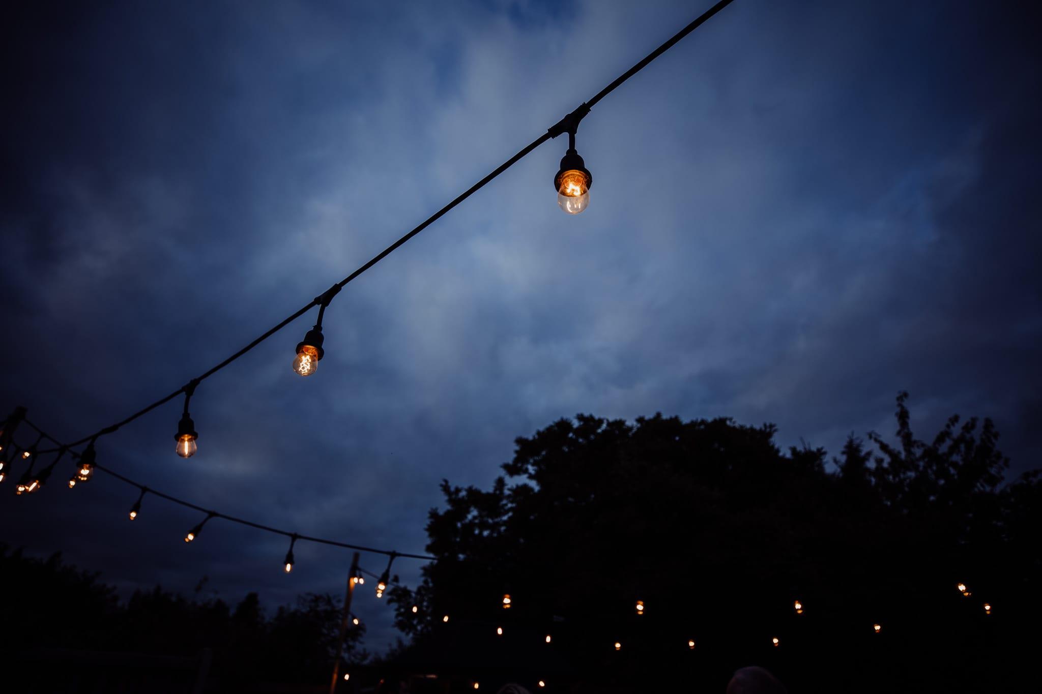 festoon lights against evening sky at an Essex back garden wedding