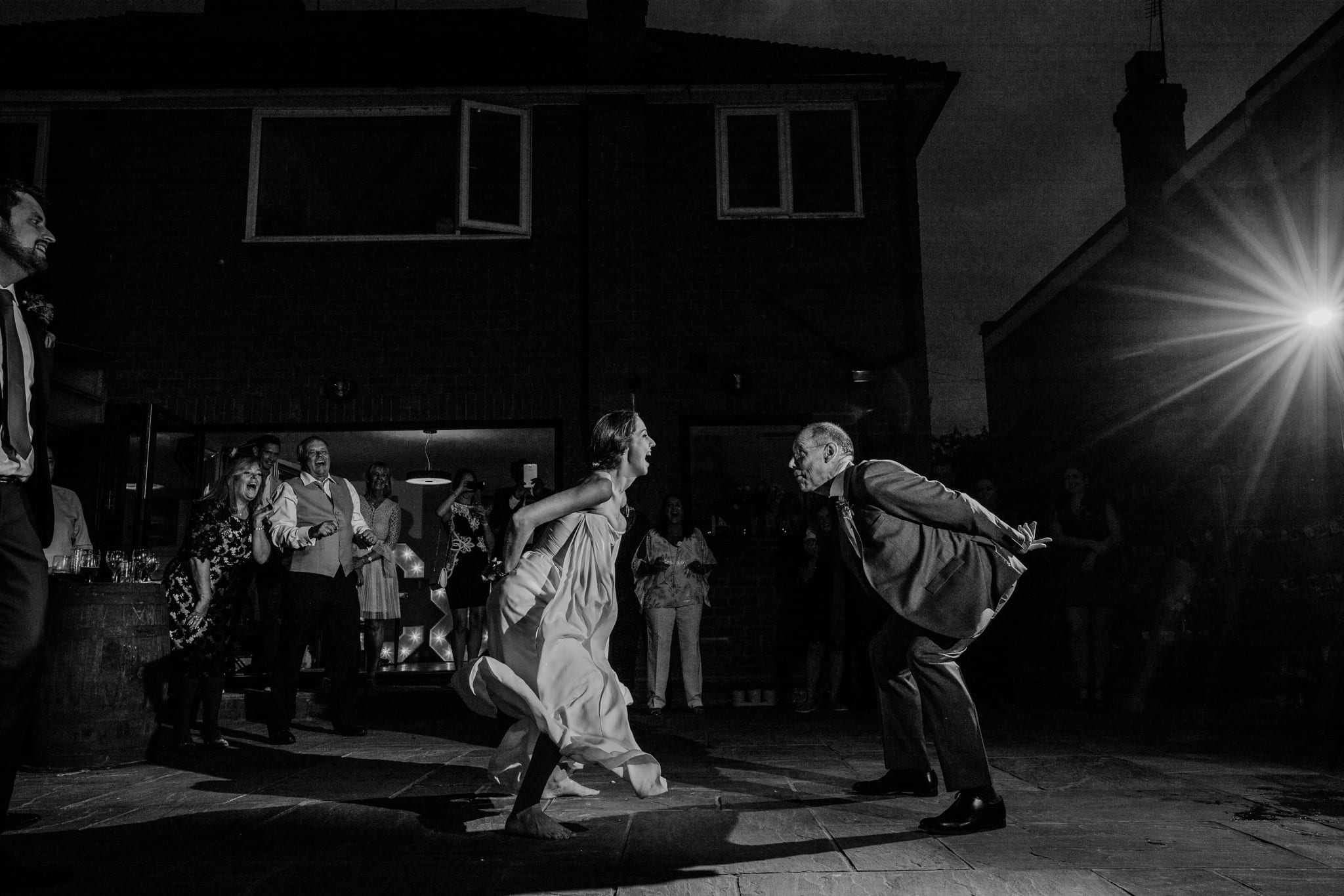 father and daughter first dance with guests watching at a back garden wedding