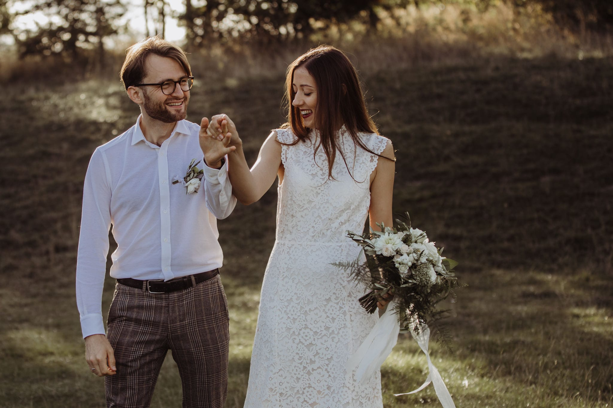 bride and groom holding hand on a meadow