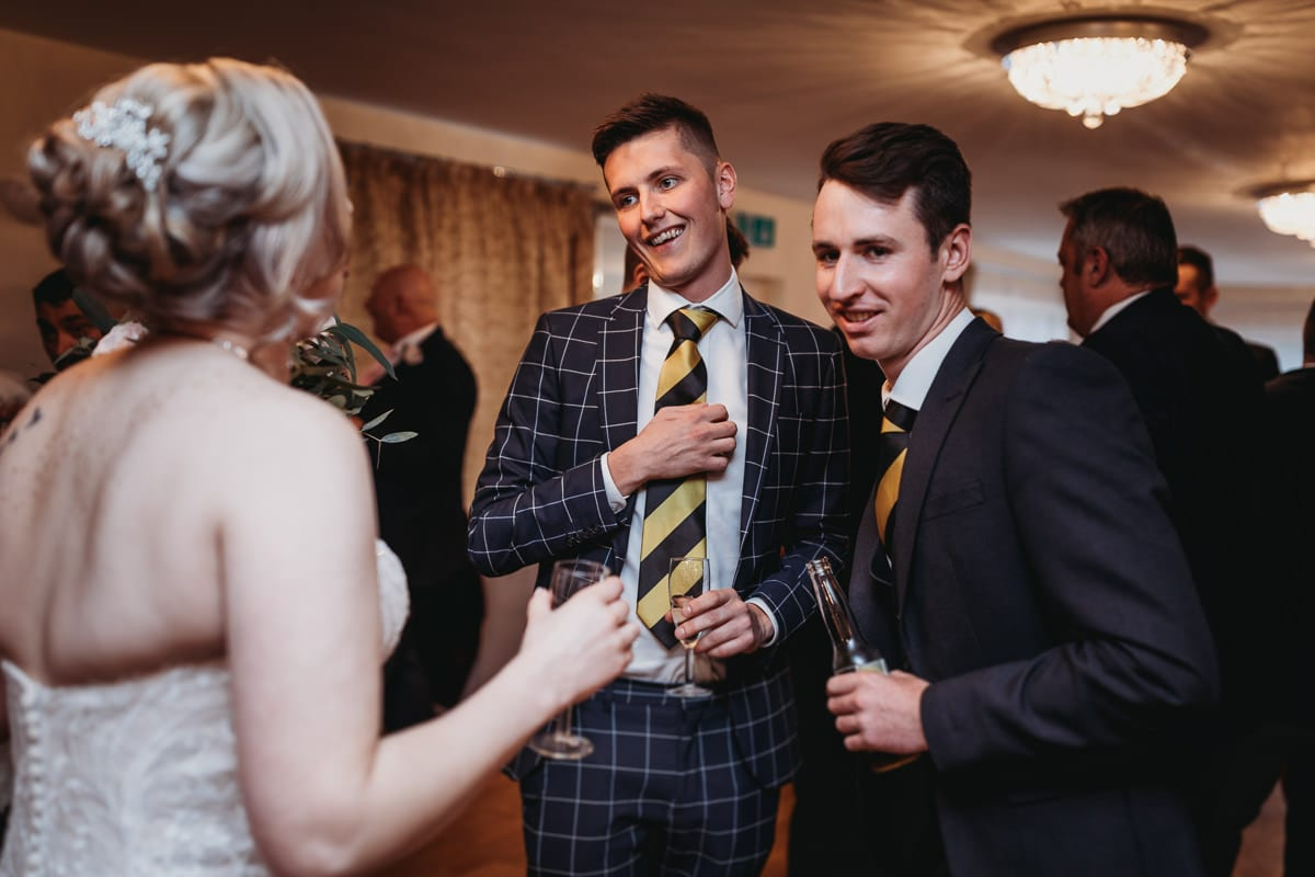 young men chatting to bride