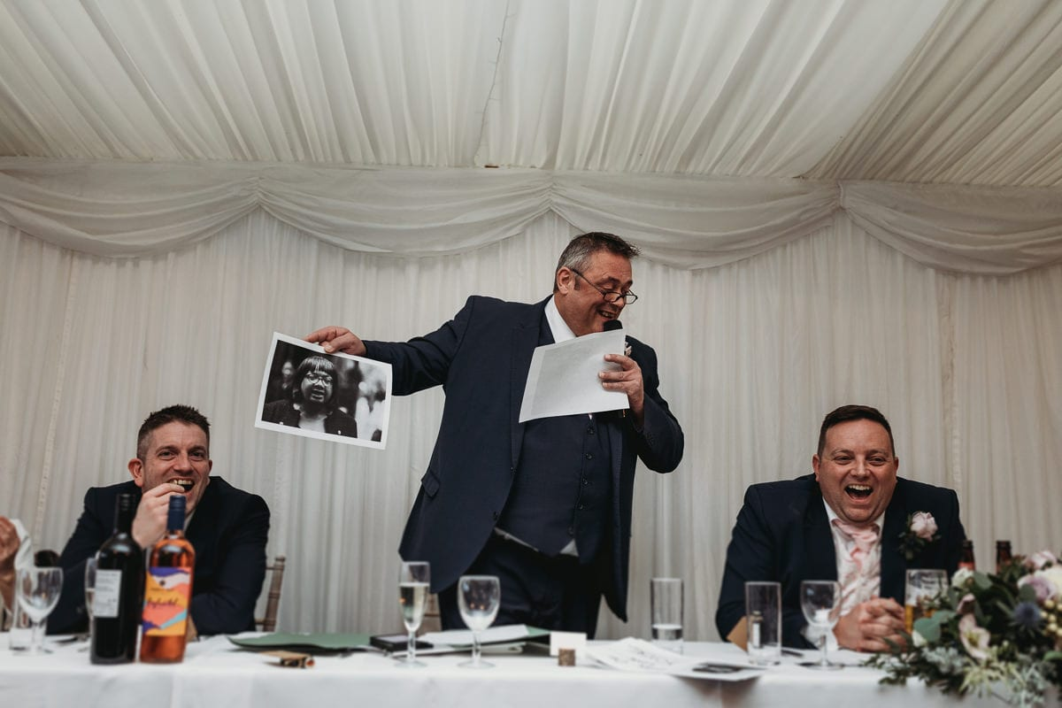 man showing photo and others laughing