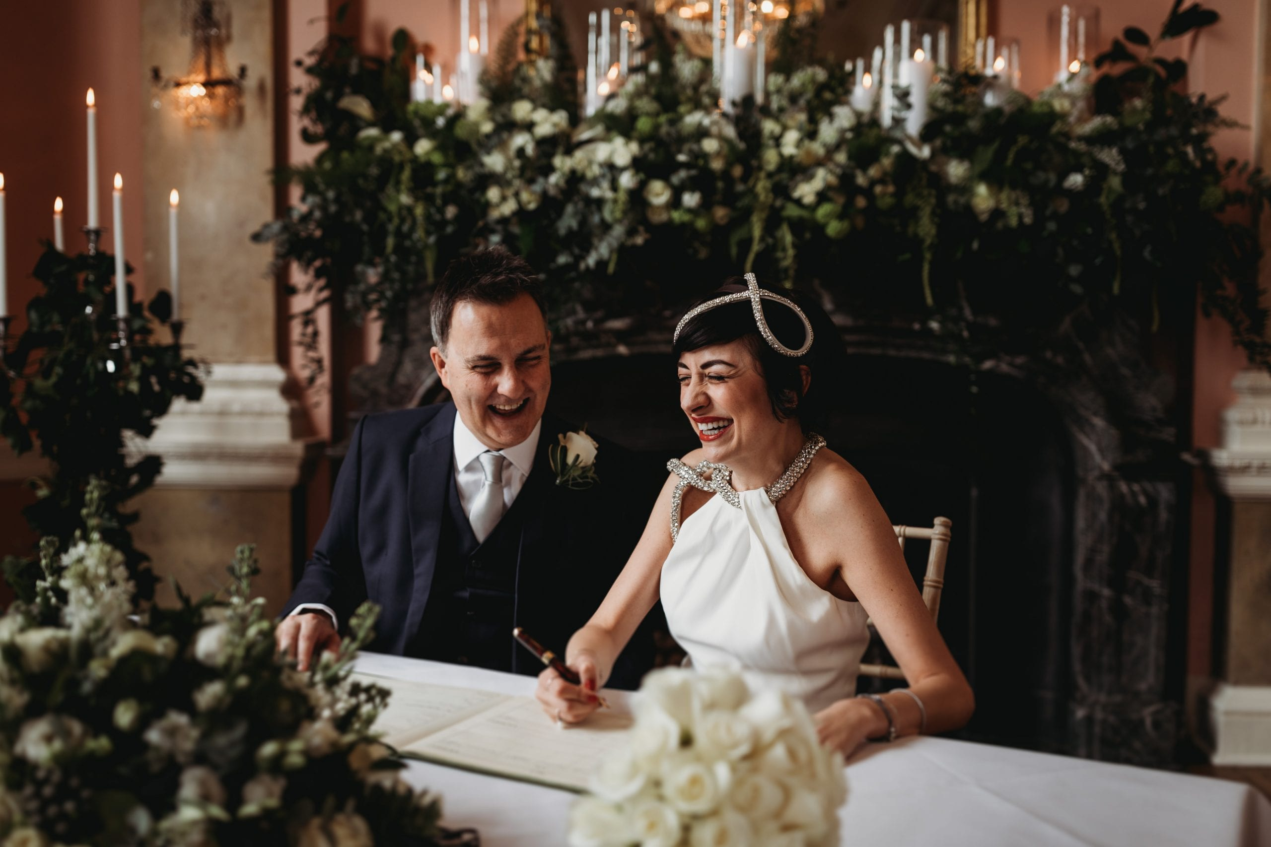 bride and groom laughing whilst signing