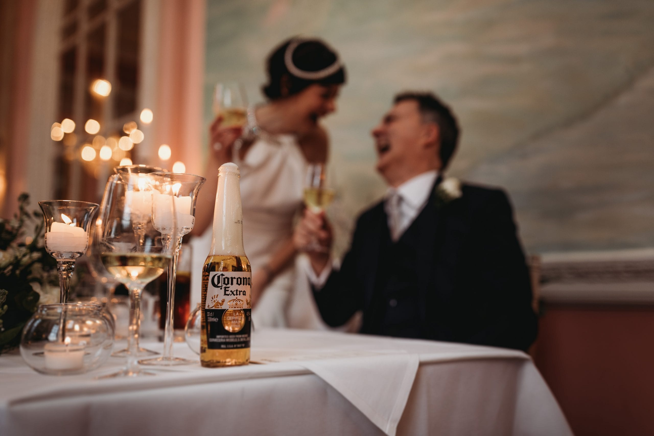 bride and groom laughing and beer in front of them