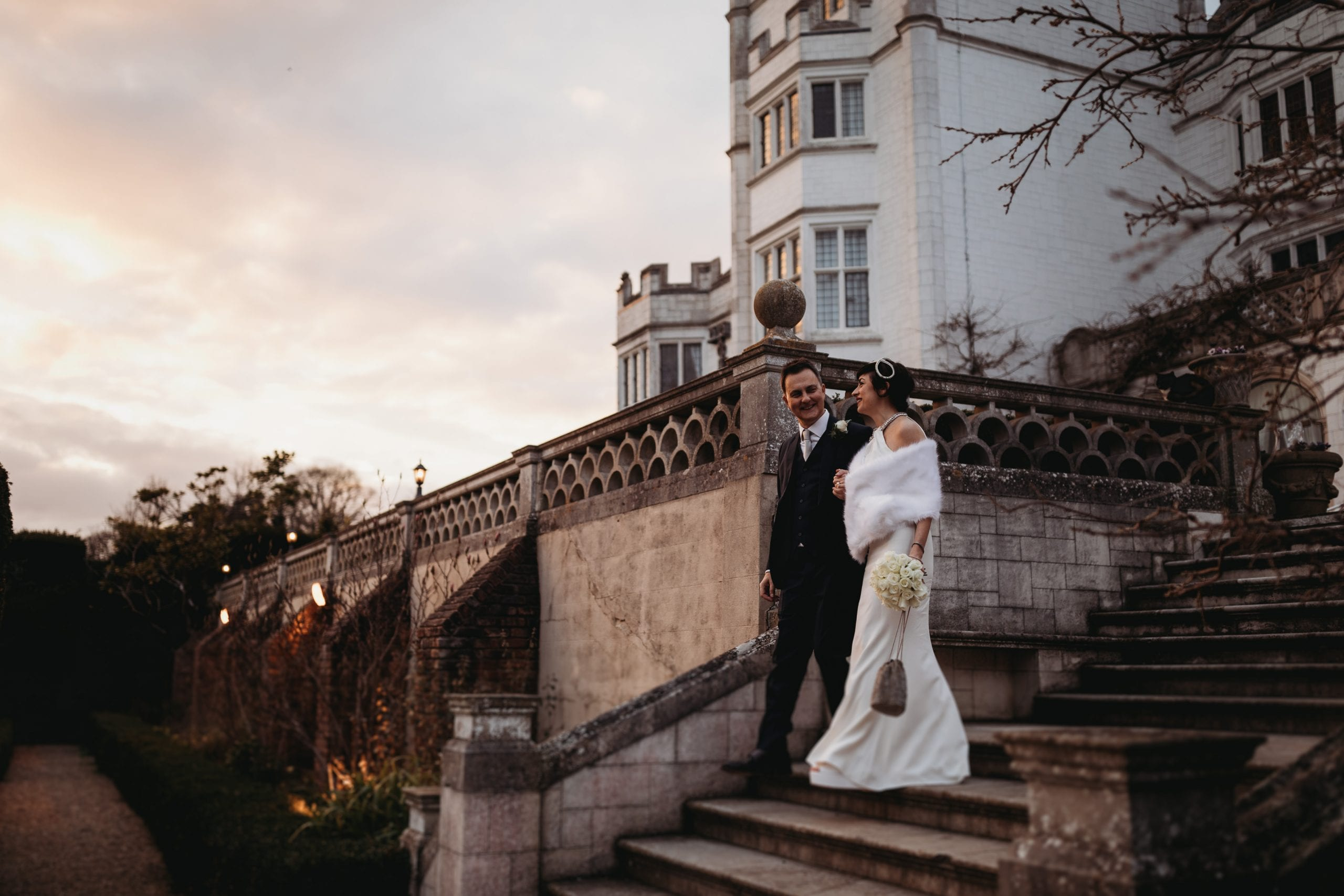 bride and groom walking down stairs outside at their Danesfield House wedding