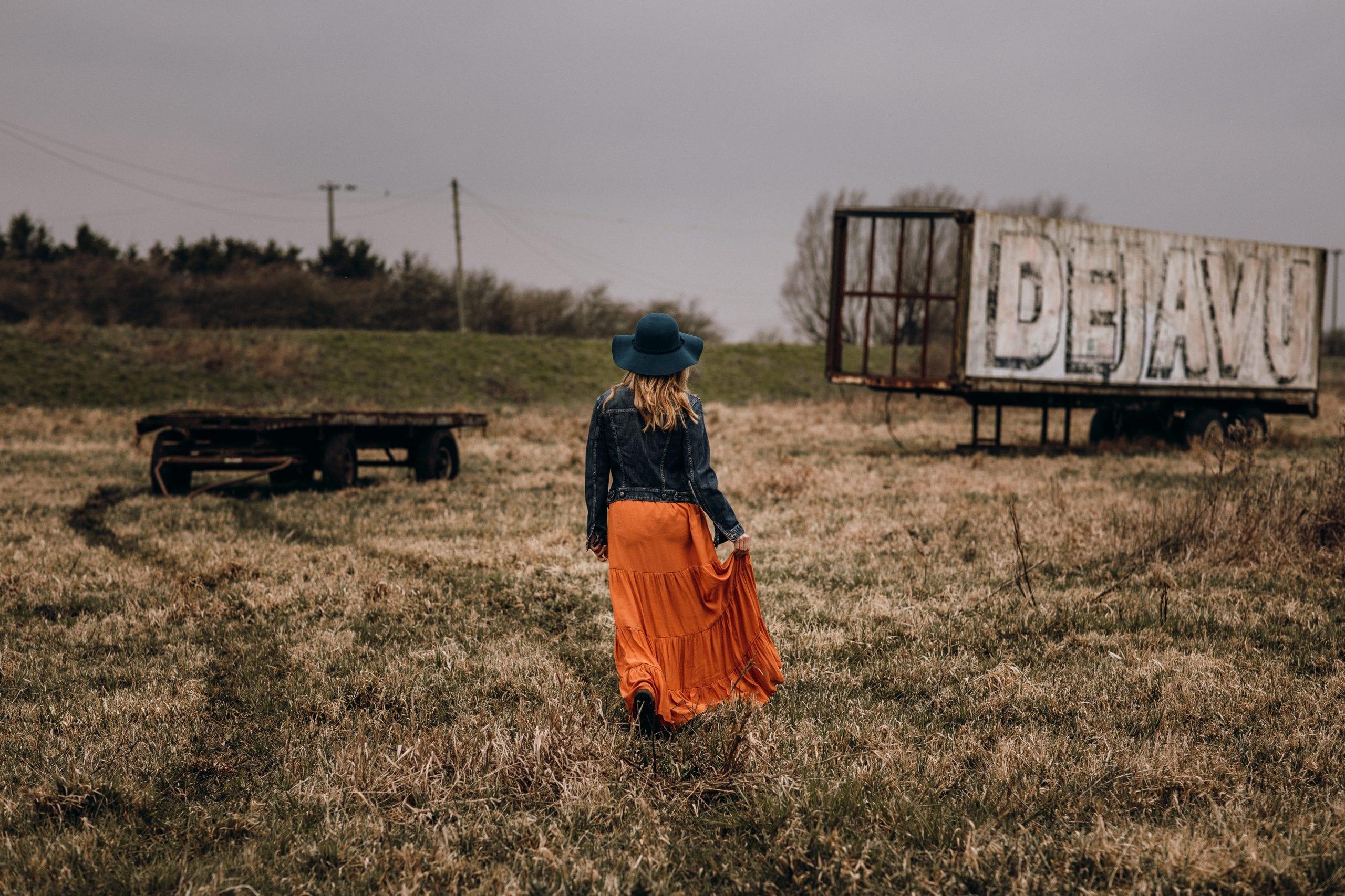 woman walking on a field towards abandoned truck